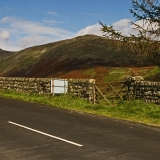 A road, a fence and mountains at Lake District