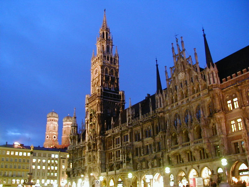The illuminated Munich city hall at Marienplatz, the cathedral towers in the background