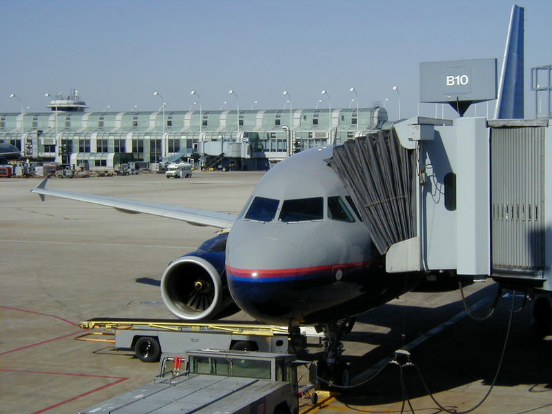 A United Airlines airplane connected to a pedestrian tube at the terminal