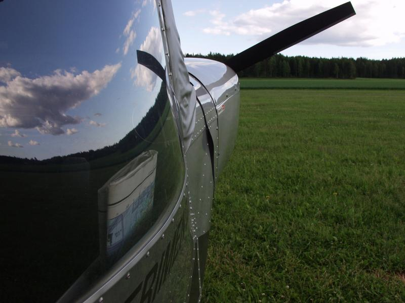 The sky reflects from the windshield of an experimental airplane