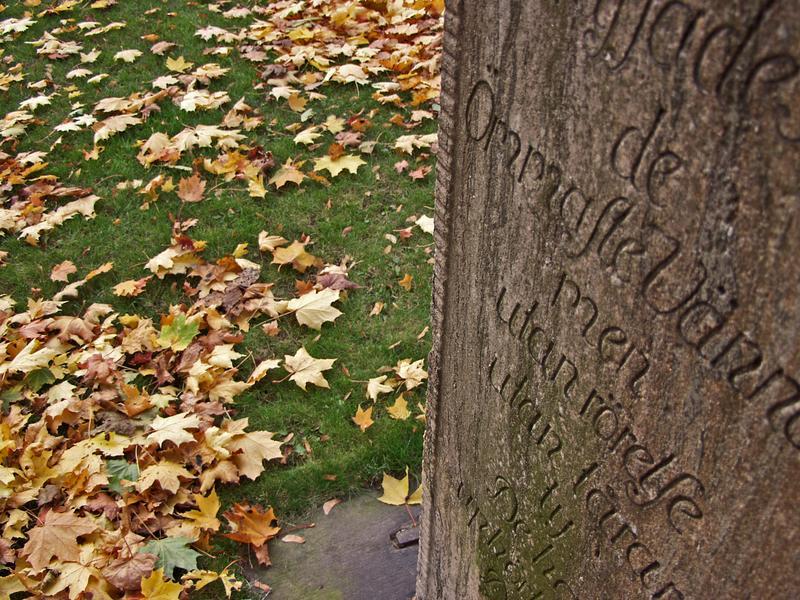 Hautakivi ja lehtipeitteistä nurmikkoa Vanhan kirkon puistossa
