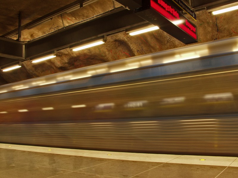 A subway train passing by a station