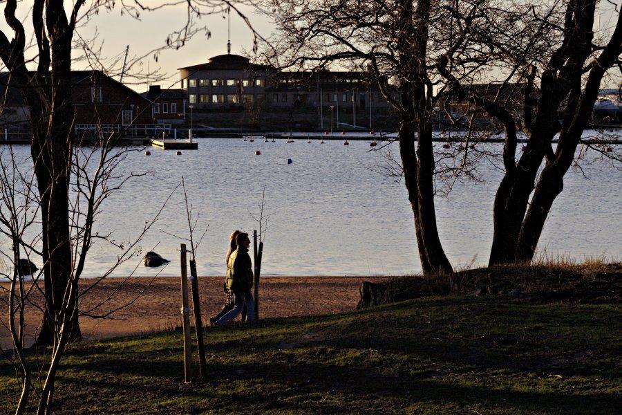 Pariskunta kävelyllä Uunisaaressa, taustalla Sirpalesaari