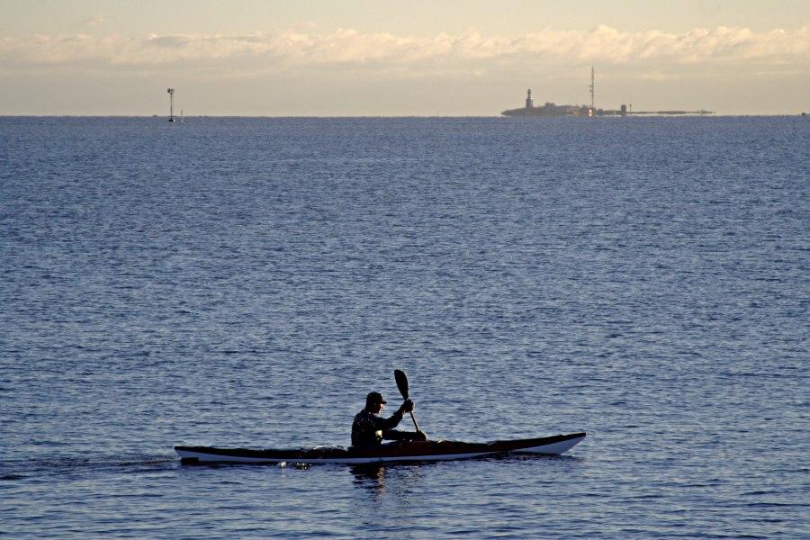 A paddler passes Uunisaari island, Harmaja light house in the background
