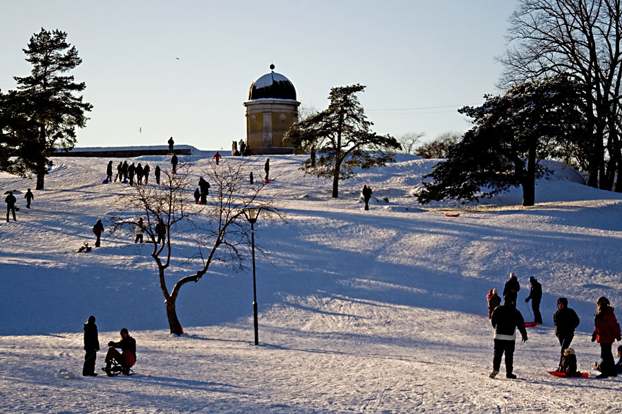 People sliding down the hill in a wintery Kaivopuisto park