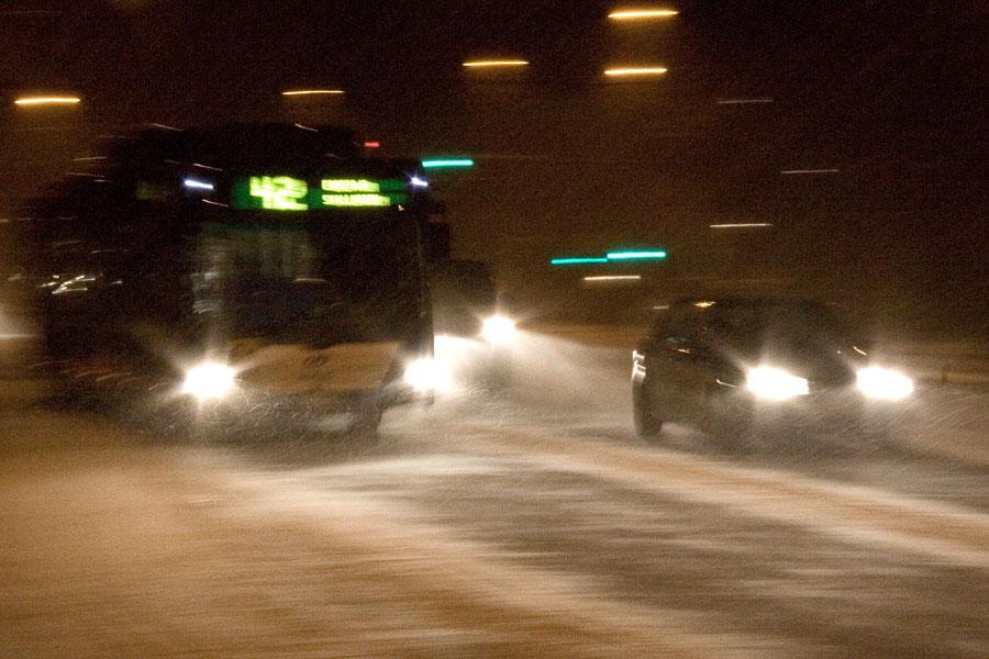 Bussi ja autoja lumimyräkässä Mannerheimintiellä