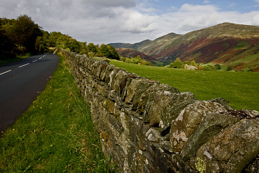 A road, a stone wall and a valley