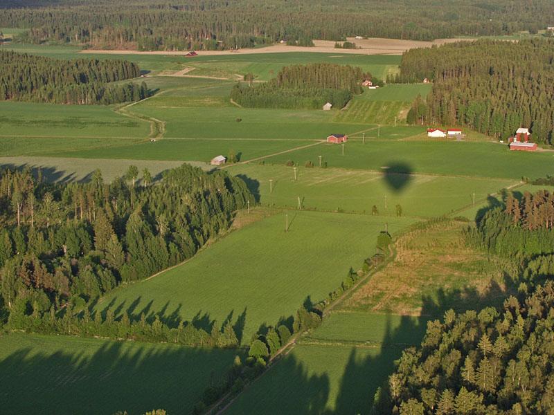 The shadow of a hot air balloon in a farmland scenery