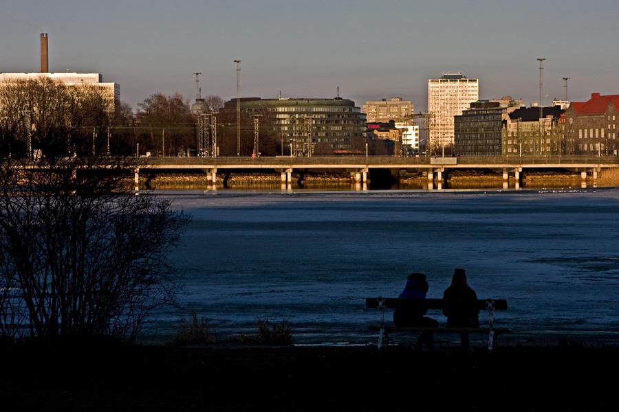 Laskeva aurinko heijastuu Hakaniemen rakennuksista Töölönlahdelle