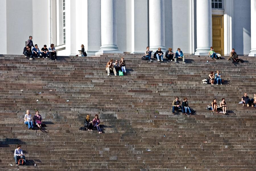 Kesäpäivän viettäjiä Tuomiokirkon portailla